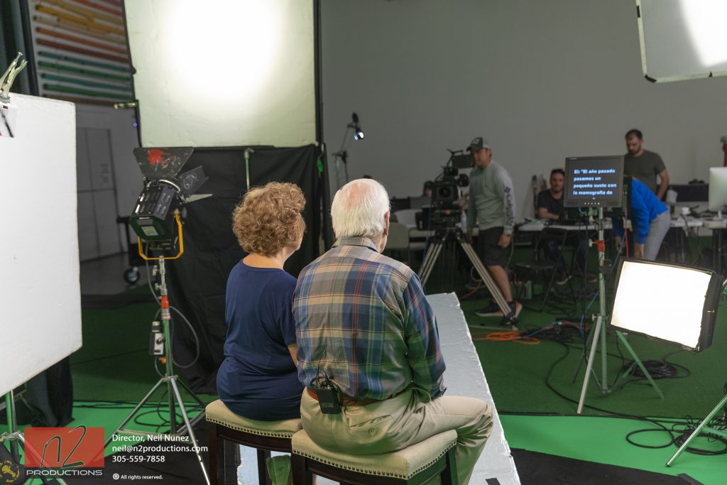 Behind the scenes at a video production studio of a tv commercial shoot with two senior citizens reading a teleprompter.